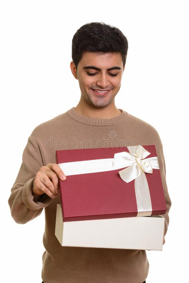 Young happy Persian man opening gift box ready for Valentine`s d. Ay stock images