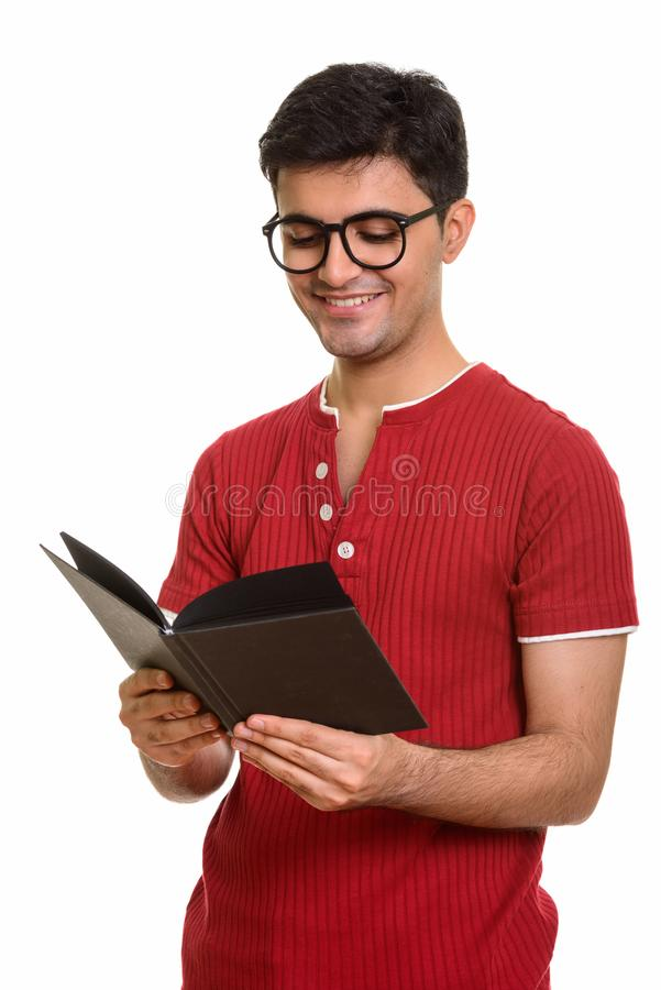 Young happy Persian man reading book while smiling stock image