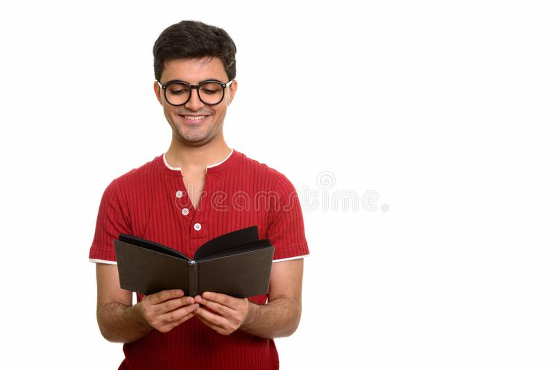 Young happy Persian man reading book while smiling stock photos