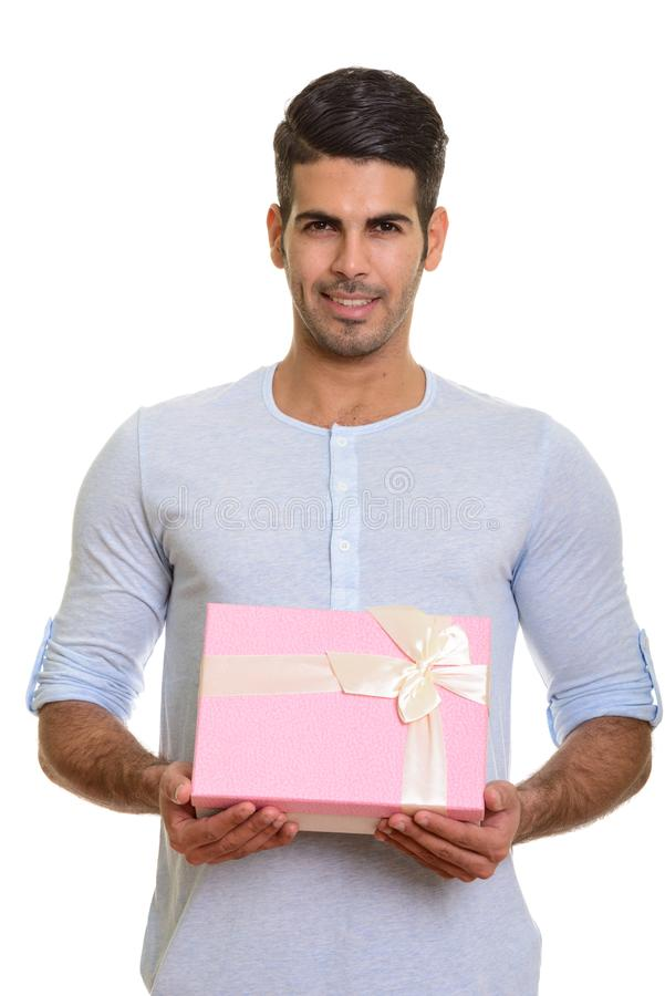 Young happy Persian man smiling and holding gift box royalty free stock image
