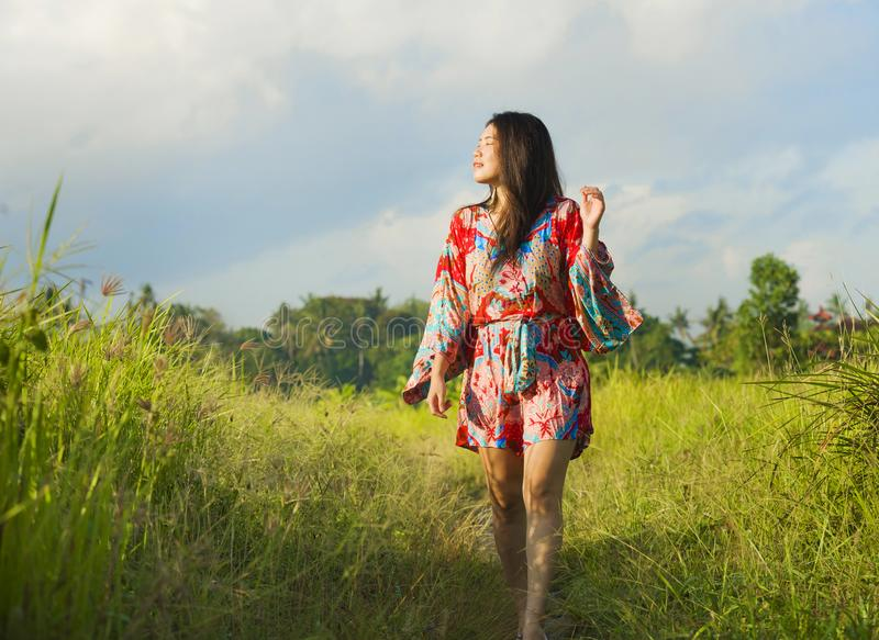 Young happy and playful Asian Chinese woman in beautiful dress having fun enjoying holidays excursion on grass tropical field smil royalty free stock images