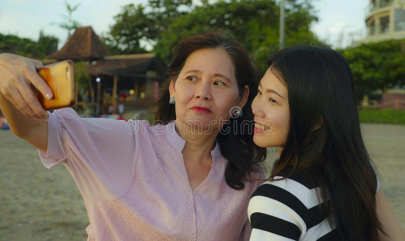 Young happy and pretty Asian Chinese girl on the beach taking selfie photo with her mother, a 60s mature woman , enjoying Summer royalty free stock photo