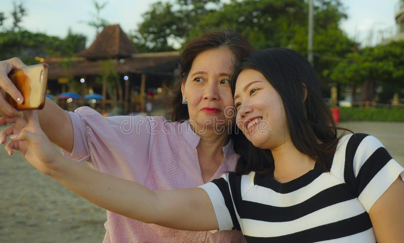 Young happy and pretty Asian Chinese girl on the beach taking selfie photo with her mother, a 60s mature woman , enjoying Summer stock image