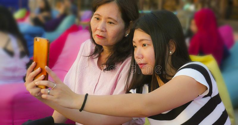 Young happy and pretty Asian Chinese girl on the beach taking selfie photo with her mother, a 60s mature woman , enjoying Summer royalty free stock images