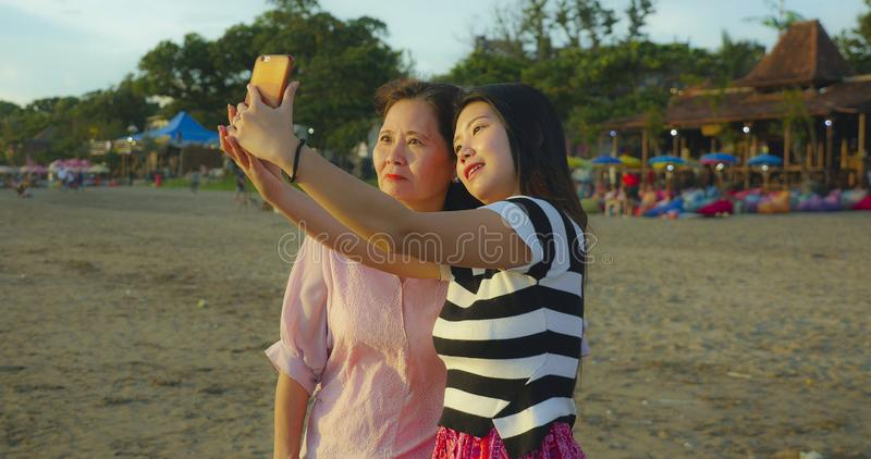 Young happy and pretty Asian Chinese girl on the beach taking selfie photo with her mother, a 60s mature woman , enjoying Summer stock photography