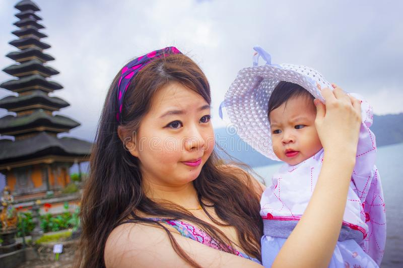 Young happy pretty Asian Chinese woman as loving mother holding adorable daughter baby girl during holidays excursion visiting royalty free stock photo