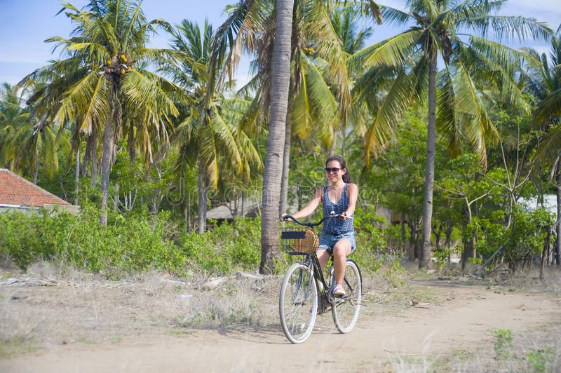 Young happy and pretty Asian Chinese woman riding bike in Vietnam or Thailand tropical jungle forest with palm trees smiling relax royalty free stock images