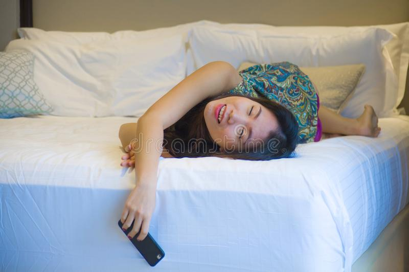 Young happy pretty Asian Korean woman at home or hotel room lying on bed relaxed smiling using internet online dating app texting. Lifestyle portrait of young stock photos