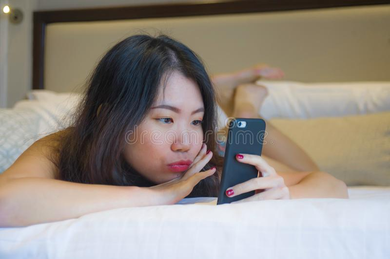 Young happy pretty Asian Korean woman at home or hotel room lying on bed relaxed smiling using internet online dating app texting. Lifestyle portrait of young stock images