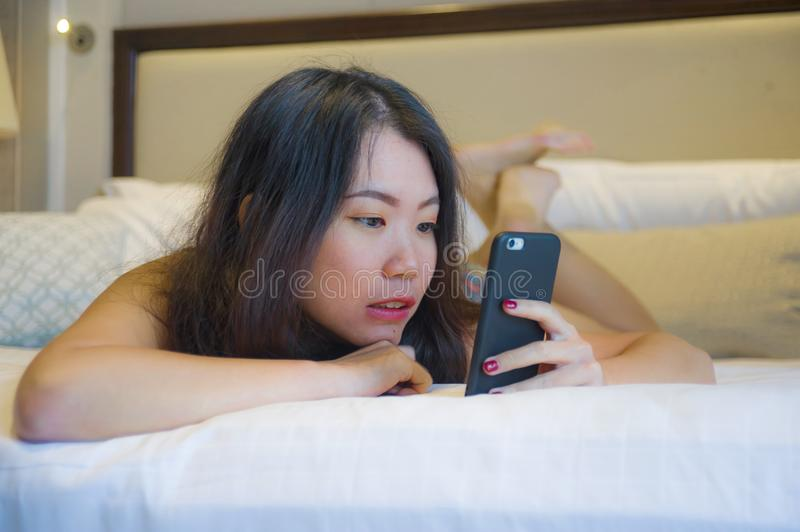 Young happy pretty Asian Korean woman at home or hotel room lying on bed relaxed smiling using internet online dating app texting. Lifestyle portrait of young royalty free stock photography