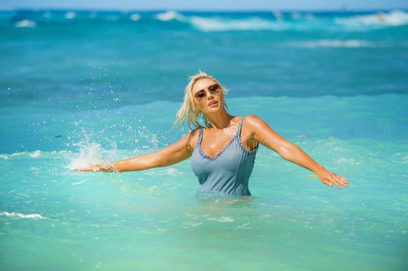 Young happy and sexy blond woman in bikini playing with waves in the sea at stunning beautiful tropical beach enjoying carefree royalty free stock image