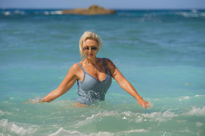 Young happy and sexy blond woman in swimsuit bikini playing with waves in the sea at stunning beautiful tropical beach enjoying royalty free stock photos