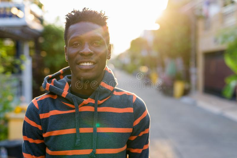 Young happy slim black African man smiling with sunlight beaming stock photo