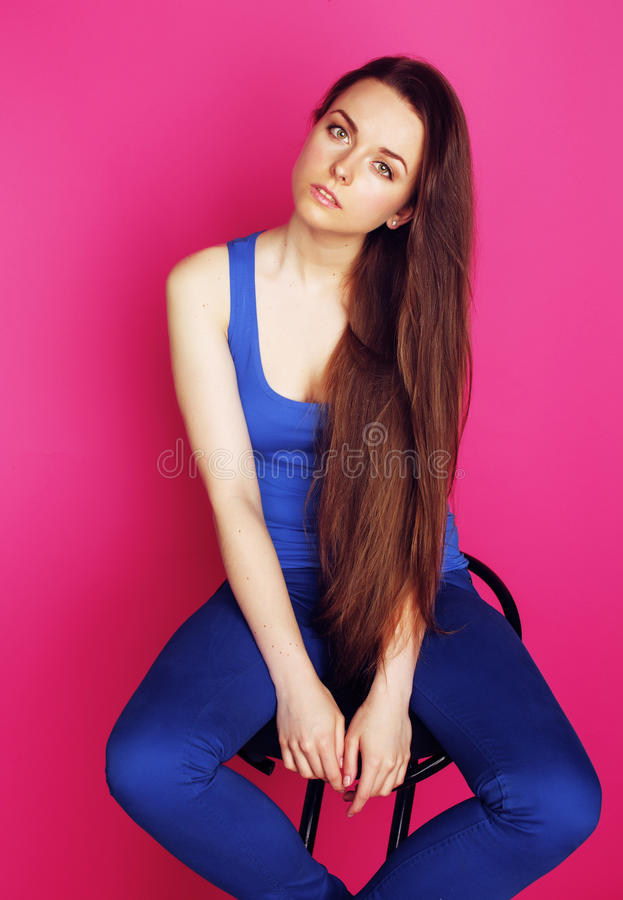 Young happy slim girl with skipping rope on pink background smil. Ing sweety cute glamour royalty free stock image