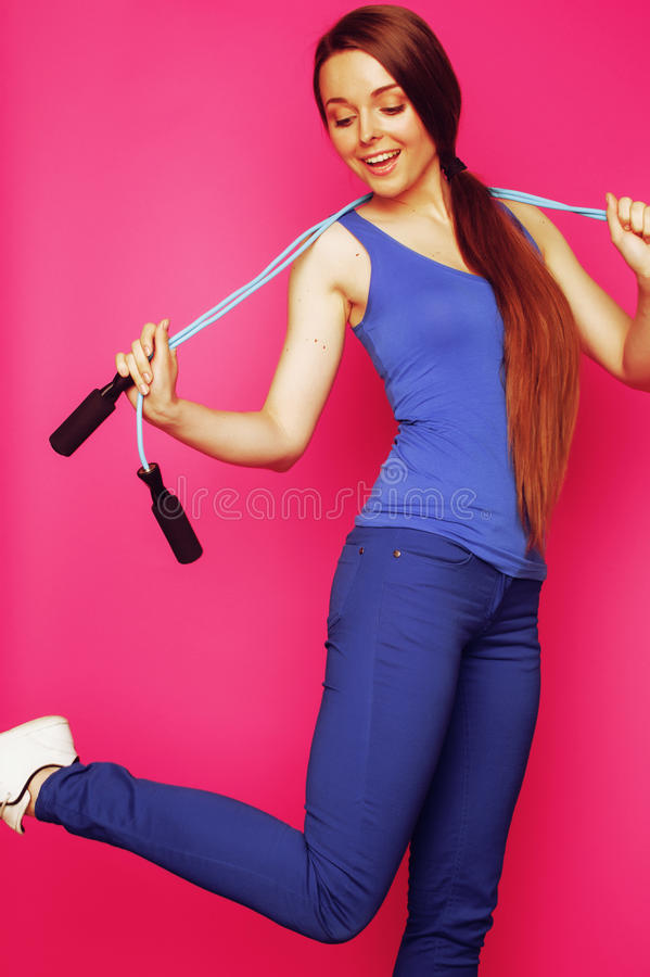 Young happy slim girl with skipping rope on pink background smil. Ing sweety cute, glamour sport wear royalty free stock photos