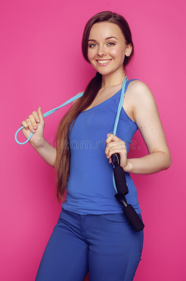 Young happy slim girl with skipping rope on pink. Background smiling sweety cute , good shape blue outfit stock photo