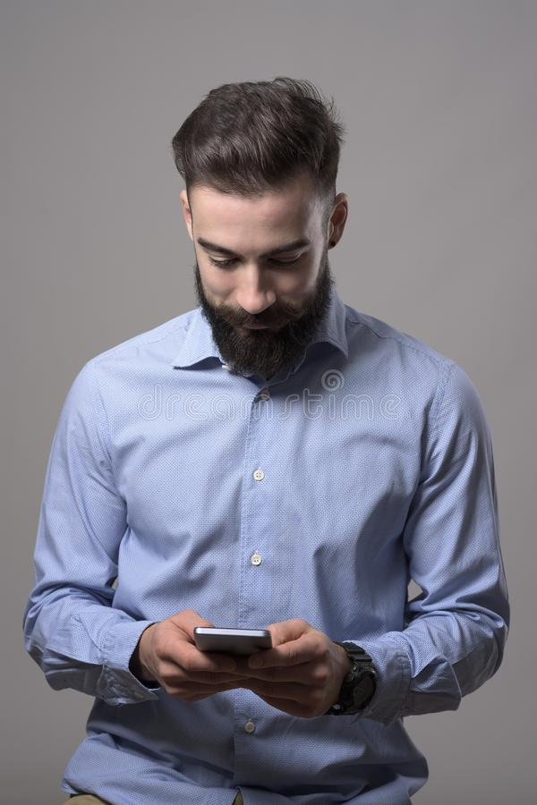 Young happy smiling bearded stylish business man typing message on mobile phone looking down at phone royalty free stock images
