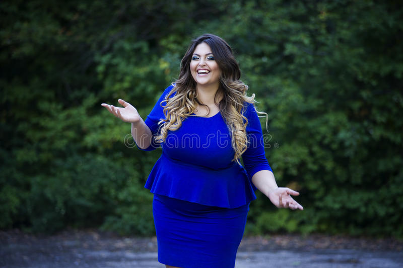 Young happy smiling beautiful plus size model in blue dress outdoors, xxl woman on nature stock photo