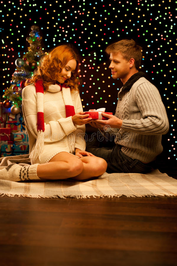 Young happy smiling casual couple making a present stock images