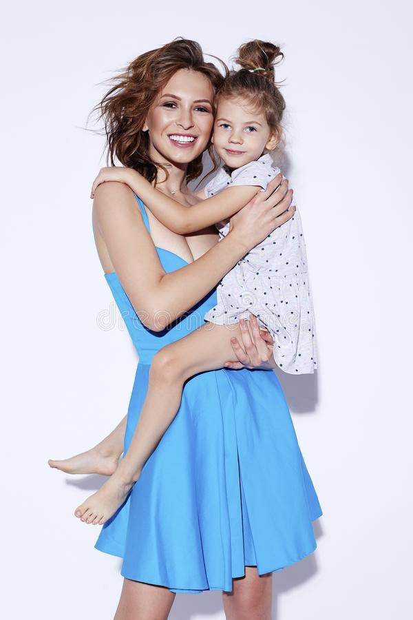 Young happy smiling cheerful mother holding her adorable little daughter looking at camera. Mother day march concept stock photos