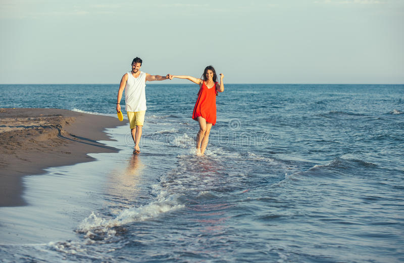 Young happy smiling couple walking on beach royalty free stock photography