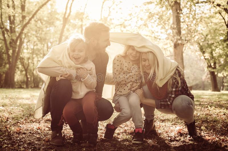Happy smiling family playing in park with blanket. stock photography