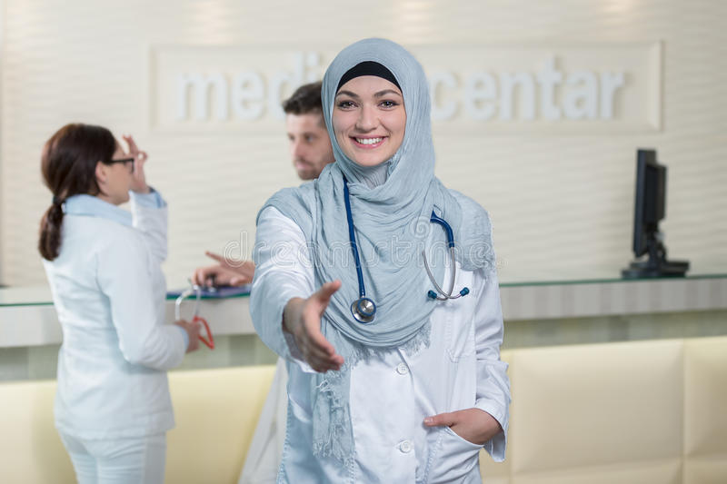 Young happy smiling female muslim doctor giving hand for handshaking. stock photography