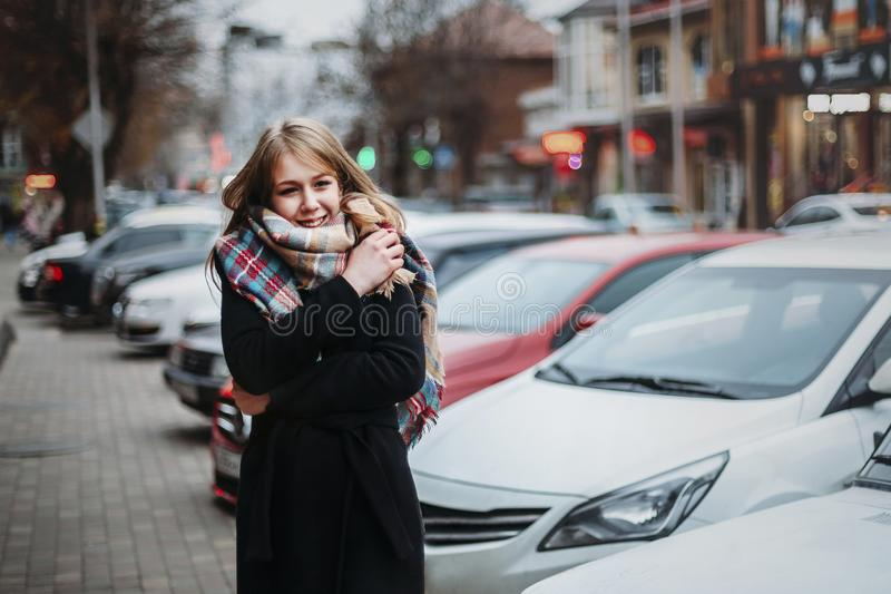 Young happy smiling woman in black coat and scarf walking around city. Waiting for her boyfriend. Waiting for meeting stock image