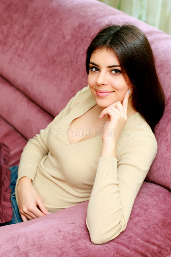 Young happy smiling woman sitting on the sofa stock images