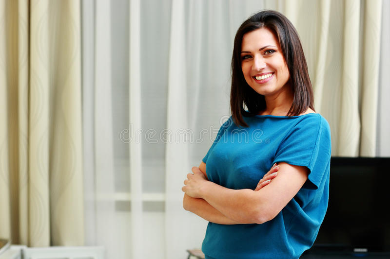 Young happy smiling woman standing with arms folded. At home royalty free stock images