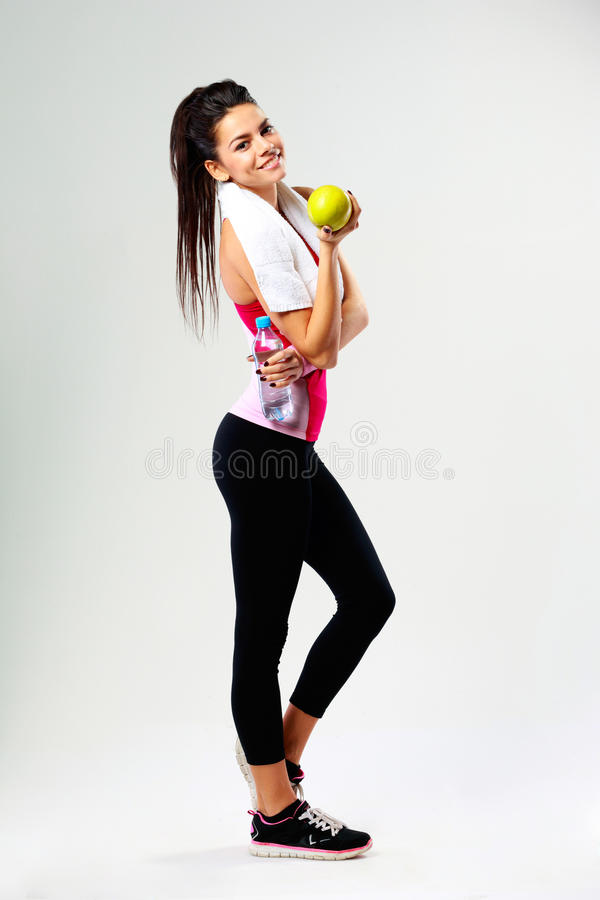 Young happy sport woman with apple and bottle of water royalty free stock photography