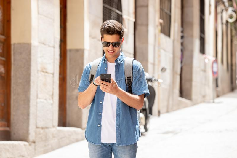Happy young student male texting on his smart phone in modern city royalty free stock photo