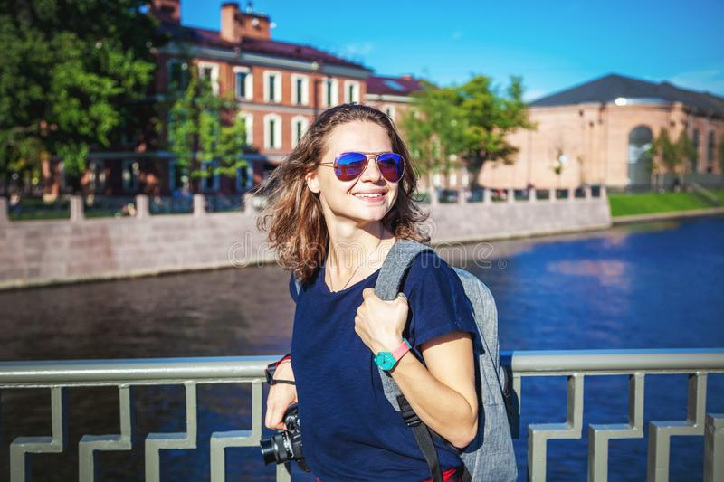 Young happy stylish girl traveler student walks around the European city with a camera in hands royalty free stock images