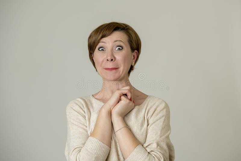 Young happy and surprised red hair woman looking to camera delighted astonished and in surprise face expression isolated on grey b stock photo