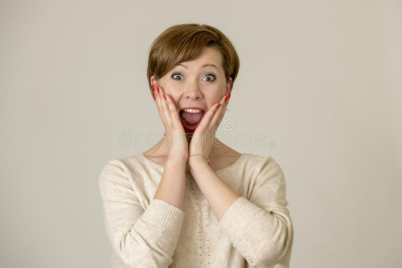 Young happy and surprised red hair woman looking to camera delighted astonished and in surprise face expression isolated on grey b. Ackground in emotions concept royalty free stock image