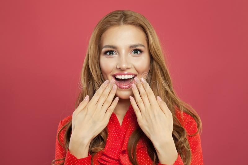 Young happy surprised woman with opened mouth. Cheerful girl on bright pink background royalty free stock photo