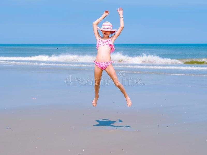 Young happy teen girl having fun on tropical beach and jumping in pink swimsuit and striped hat into the air on the sea coast royalty free stock image