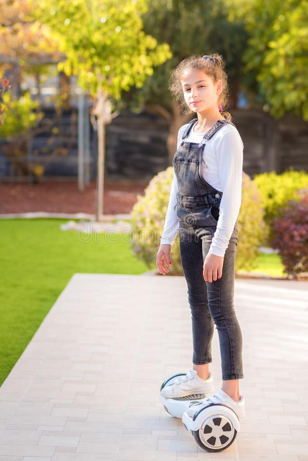 Young happy teenager girl balancing on electric hoverboard at the sunny park, sunny day. Side view. royalty free stock images