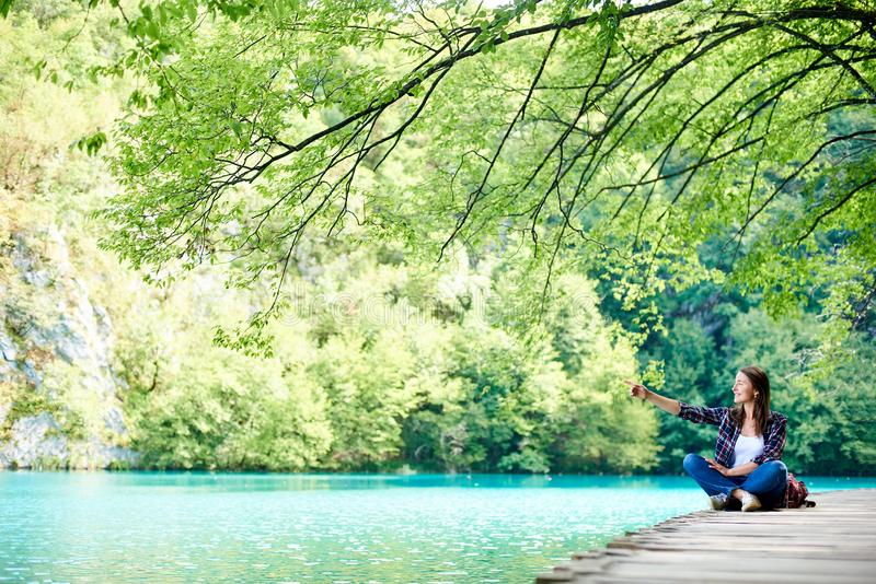 Young happy tourist woman with backpack sitting on wooden bridge enjoying beautiful view stock image