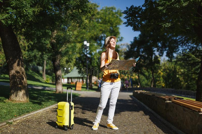 Young happy traveler tourist woman in yellow summer casual clothes, hat with suitcase city map walk in city outdoor royalty free stock photo