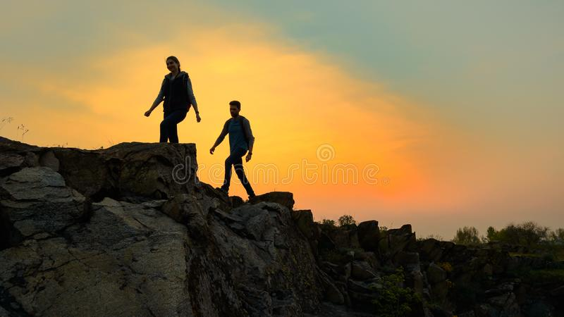 Young Happy Travelers Hiking with Backpacks on the Rocky Trail at Summer Sunset. Family Travel and Adventure Concept. royalty free stock photo