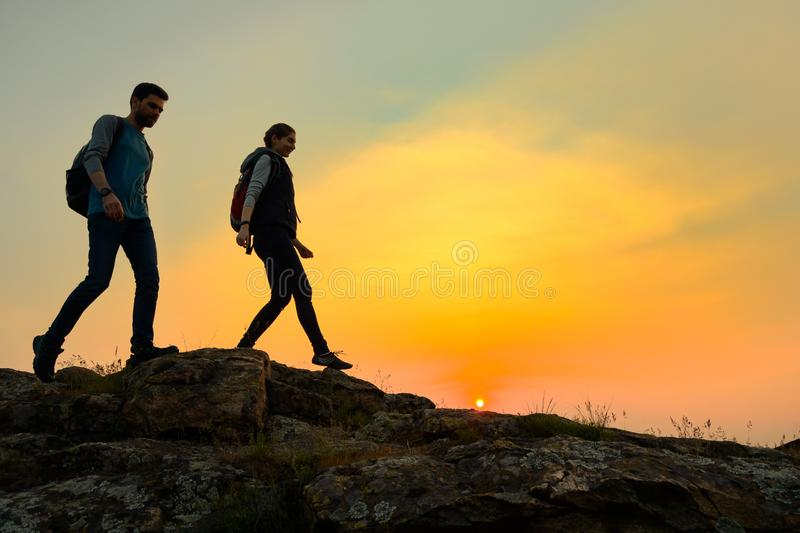 Young Happy Travelers Hiking with Backpacks on the Rocky Trail at Summer Sunset. Family Travel and Adventure Concept. stock photography