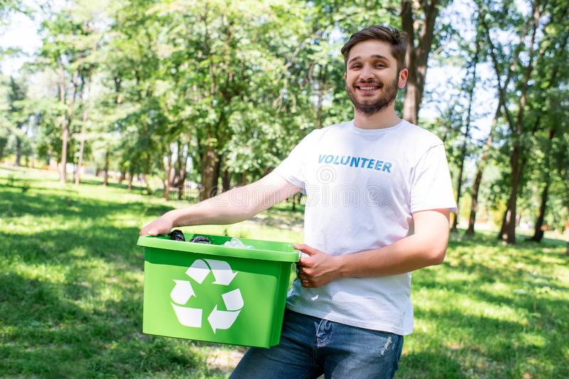 young happy volunteer holding recycling box stock image