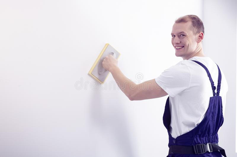 Young, happy wall painter in workwear posing, looking at the cam. Era while smoothing down a white wall with a sandpaper tool royalty free stock photo