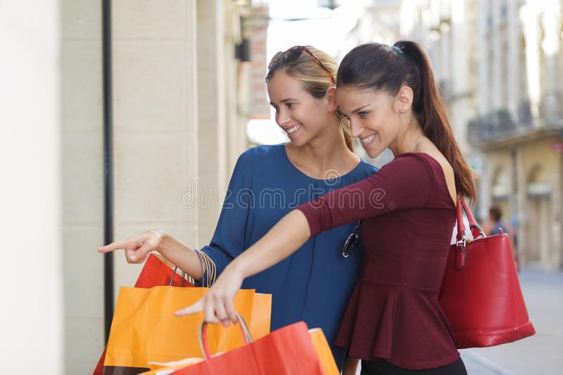 Young happy and wealthy women shopping royalty free stock photos