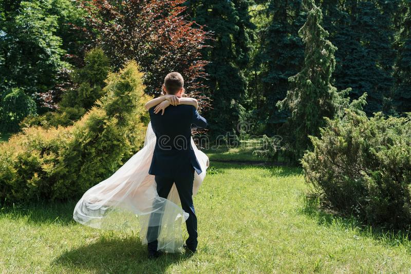 Young happy wedding couple dancing and having fun in sunny wedding day. Groom spinning bride. Dress develops in the wind. royalty free stock photos