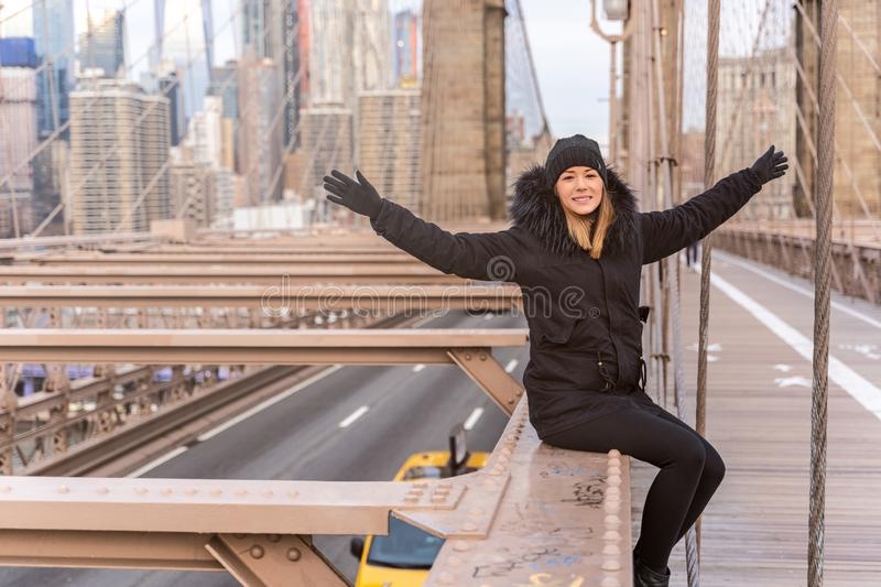 Young happy woman with arms raised on the Brooklyn bridge in New York stock images