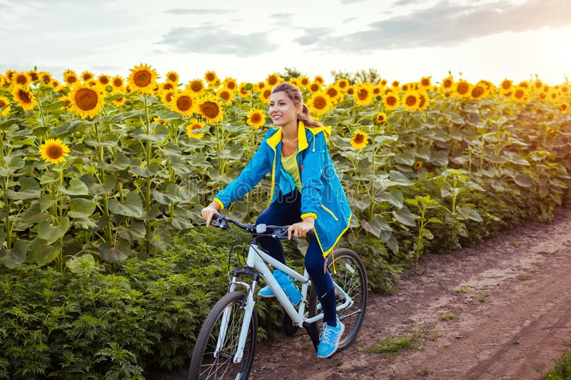 Young happy woman bicyclist riding bicycle in sunflower field. Summer sport activity. Healthy lifestyle stock images