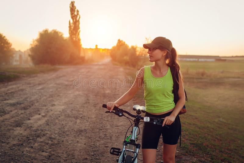 Young happy woman bicyclist riding bicycle in suburbs. Summer sport activity. Healthy lifestyle royalty free stock photo