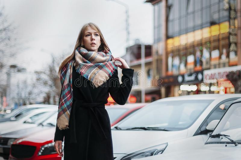 Young happy woman blonde in a black coat and scarf walks through city. Waiting for meeting stock photography